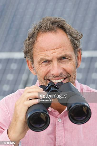Germany, Munich, Mature man holding binocular in solar plant, smiling, portrait