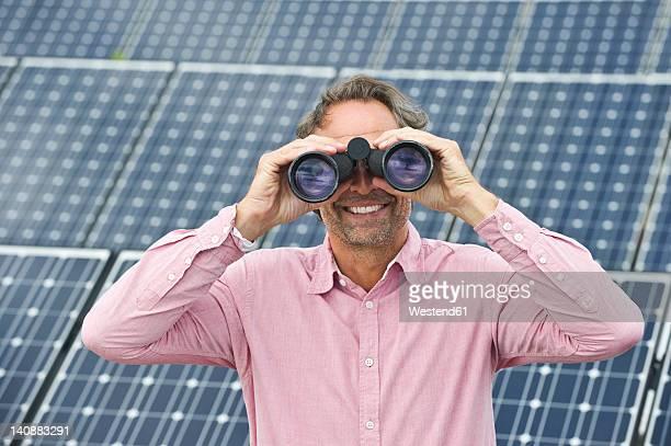 Germany, Munich, Mature man looking through binocular in solar plant, smiling