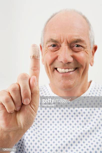 Germany, Munich, Mature man showing finger with bandage, close-up