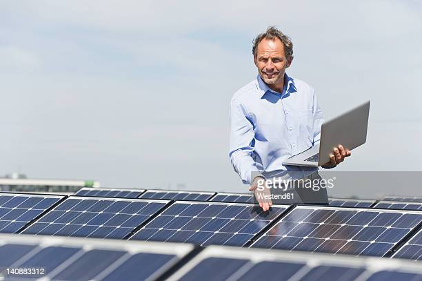 Germany, Munich, Mature man with laptop in solar plant, portrait