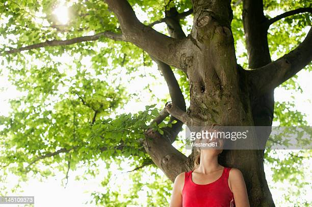 Germany, Munich, Mid adult woman resting on tree, smiling