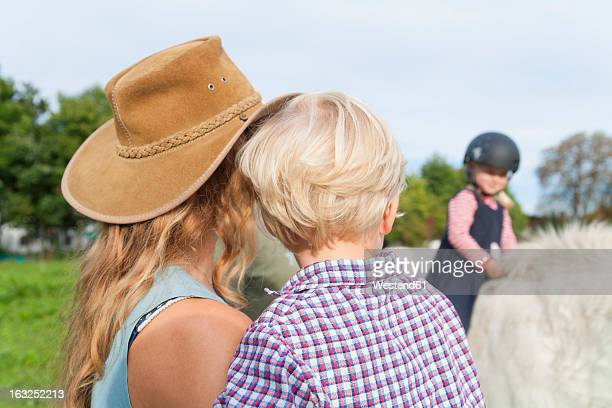 Germany, Munich, Mother and children at children's camp, daughter riding horse in background