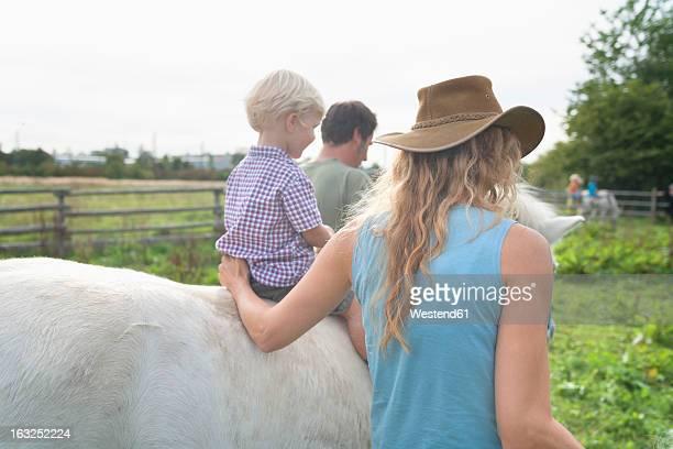 germany, munich, mother and father with son in children's camp - pony play bildbanksfoton och bilder