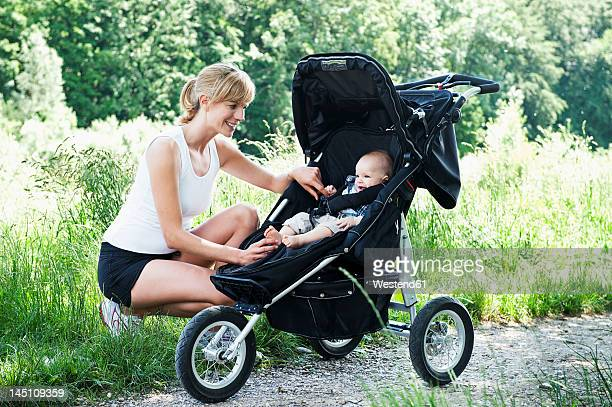 Germany, Munich, Mother crouching near baby boy, smiling