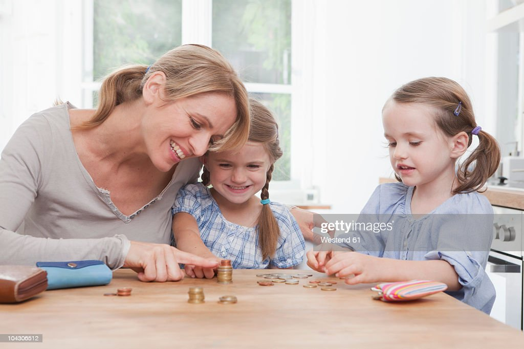 Germany, Munich, Mother with daughters (4-7) counting stack of coins : Stockfoto