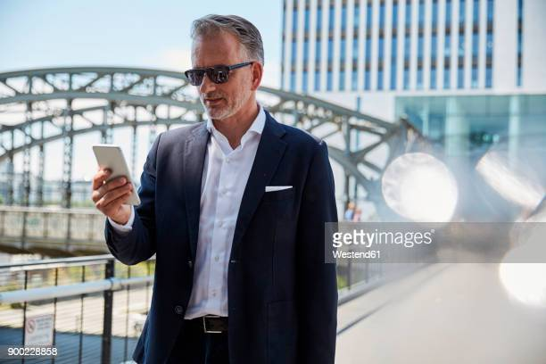 Germany, Munich, portrait of businessman wearing sunglasses looking at cell phone
