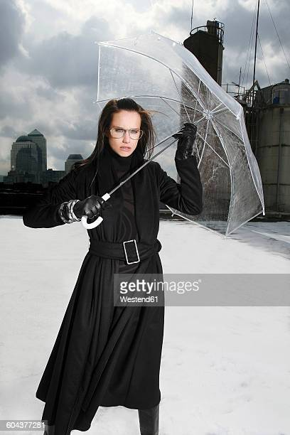 Germany, Munich, portrait of woman wearing black clothes standing on a roof with transparent umbrella