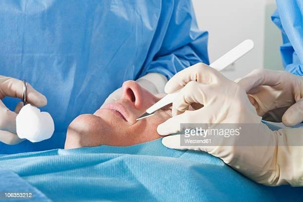 germany, munich, surgeons performing operation - 美容整形手術 ストックフォトと画像