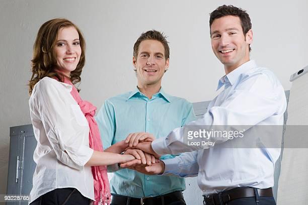 Germany, Munich, Three business people standing in office, taking oath, portrait