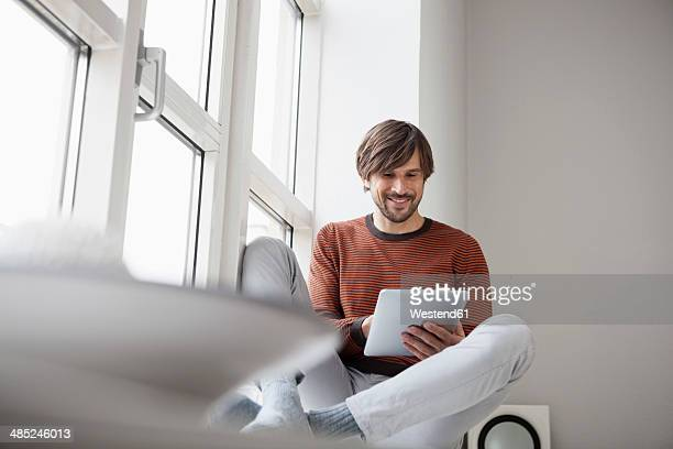 Germany, Munich, Using digital tablet, sitting on window sill