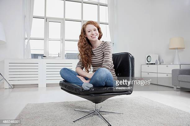 Germany, Munich, Woman at home, sitting in chair cross-legged