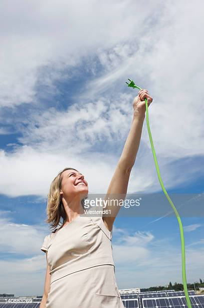 Germany, Munich, Woman holding electric cord in solar energy, smiling