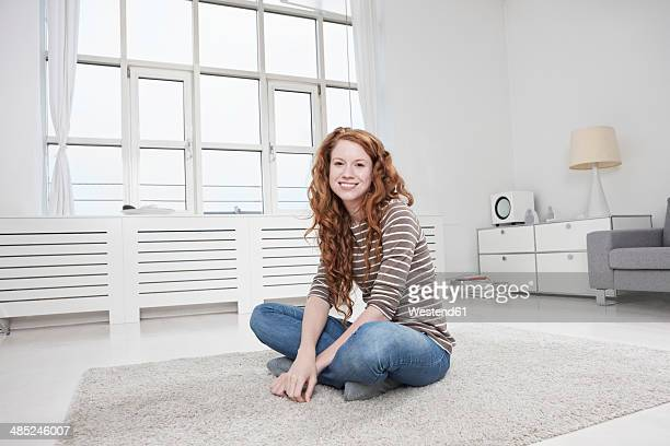 Germany, Munich, Woman sitting on  floor in living room