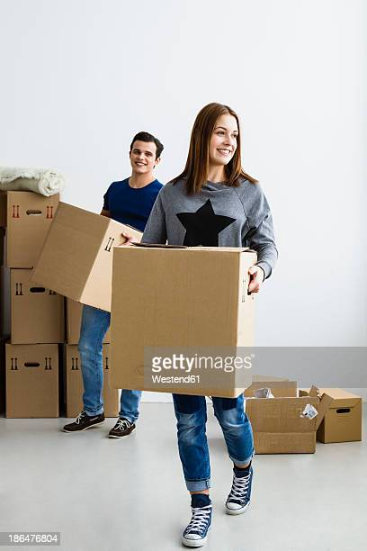 Germany, Munich, Young couple holding cardboard box, smiling