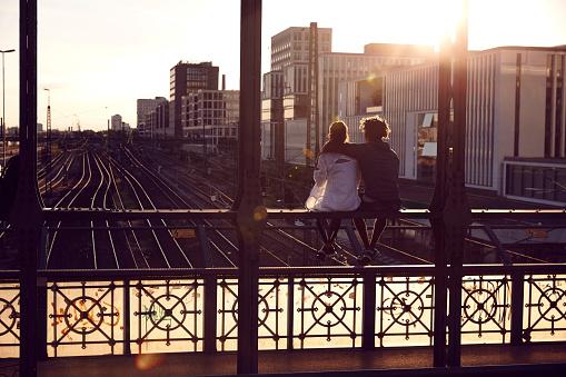 Germany, Munich, Young couple sitting on bridge, enjoying sunset - gettyimageskorea