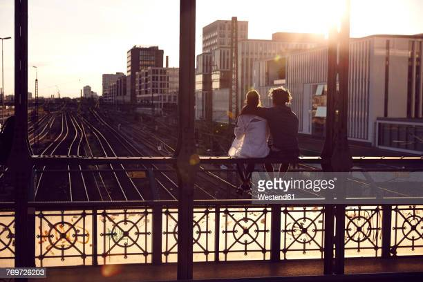 germany, munich, young couple sitting on bridge, enjoying sunset - münchen stock-fotos und bilder