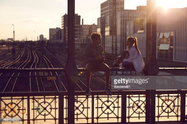 Germany, Munich, Young couple sitting on bridge, enjoying sunset