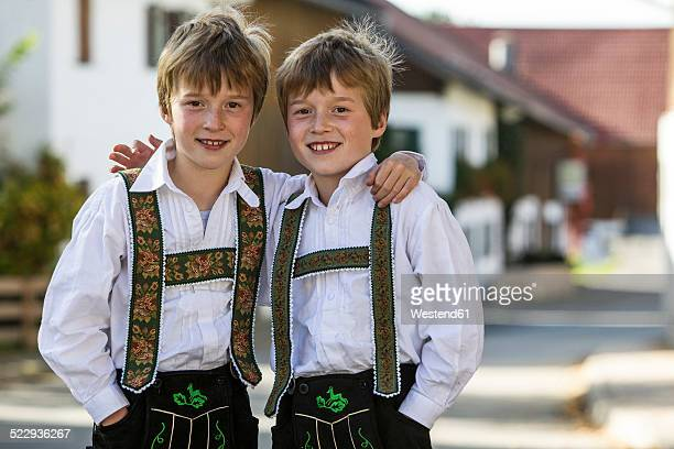 Germany, Murnau, Twin brothers wearing traditional costumes