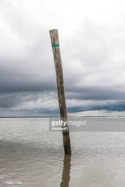 germany, nessmersiel, wooden stake in the sea - paal stockfoto's en -beelden