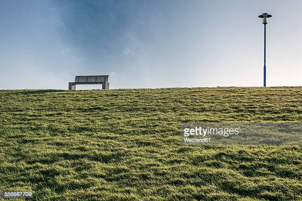 Germany, Neuharlingersiel, empty bench on dike