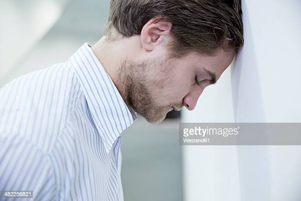 Germany, Neuss, Business man leaning head to wall