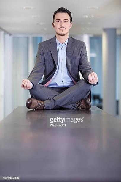 germany, neuss, business man sitting cross-legged on table - 胡坐 ストックフォトと画像