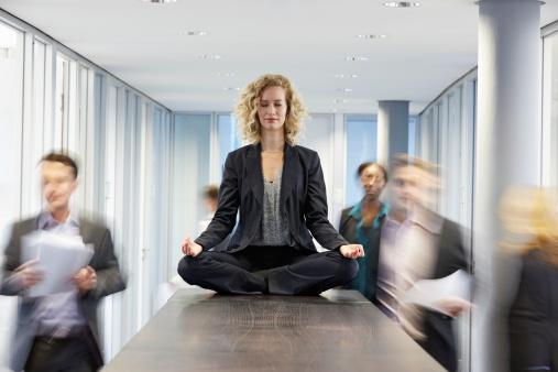 Germany, Neuss, Business woman meditating on desk - gettyimageskorea
