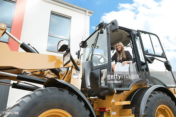Germany, Neuss, Real estate agent driving wheeled loader on construction site
