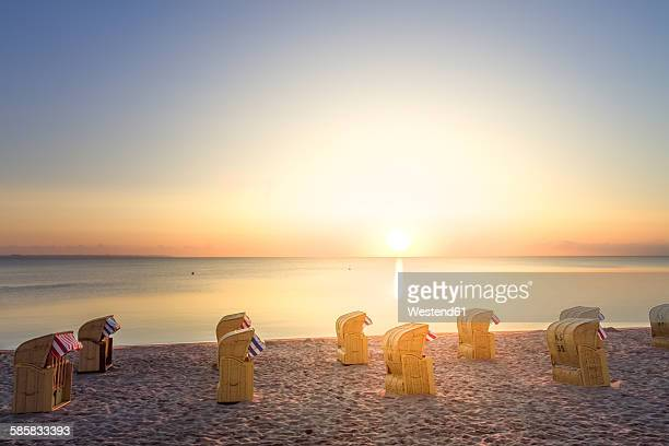 Germany, Niendorf, view to Timmendorfer Strand with hooded beach chairs at sunrise