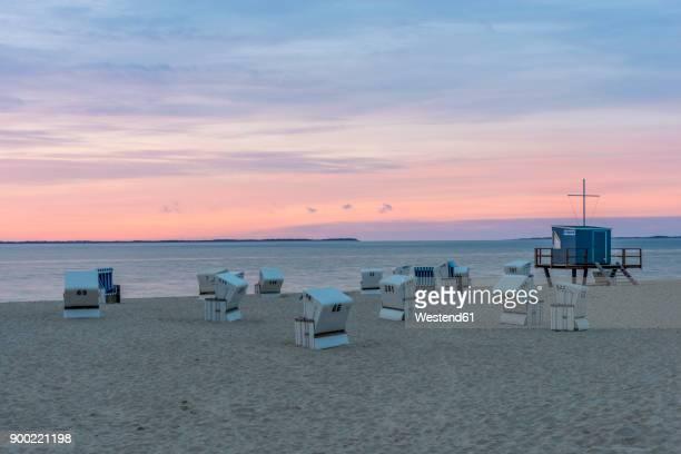 germany, north frisia, sylt, hoernum, beach with hooded beach chairs at sunrise - osten stock-fotos und bilder