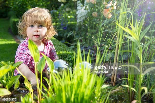 Germany, North Rhine Westphalia, Baby girl playing near garden pond