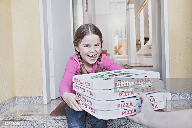 Germany, North Rhine Westphalia, Cologne, Girl taking pizza boxes from delivery man, smiling