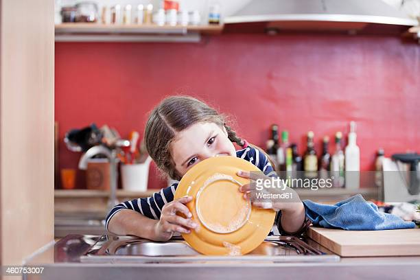 Germany, North Rhine Westphalia, Cologne, Girl washing plates in kitchen sink, close up