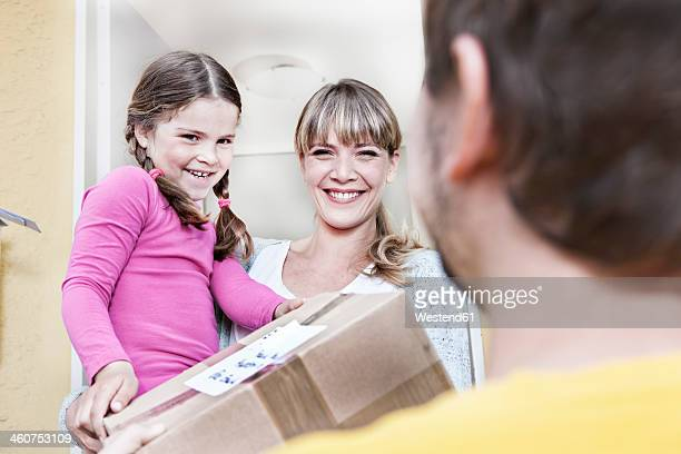 Germany, North Rhine Westphalia, Cologne, Mother and daughter taking letters from postman, smiling