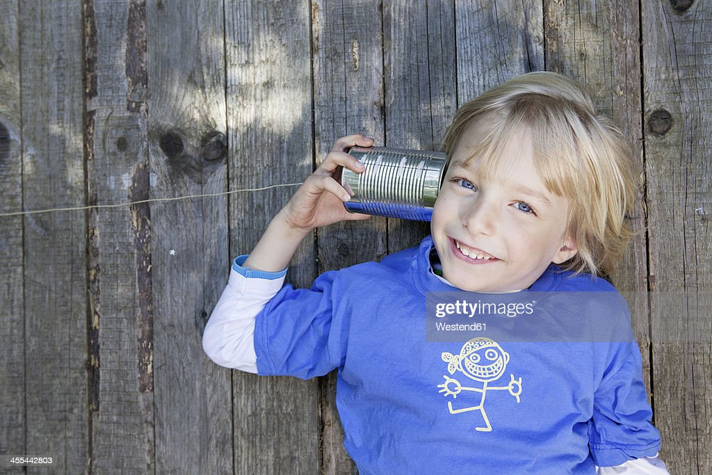 Germany, North Rhine Westphalia, Cologne, Portrait of boy listening to tin can phone, smiling : Stock Photo