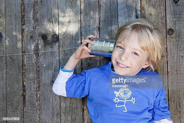 Germany, North Rhine Westphalia, Cologne, Portrait of boy listening to tin can phone, smiling