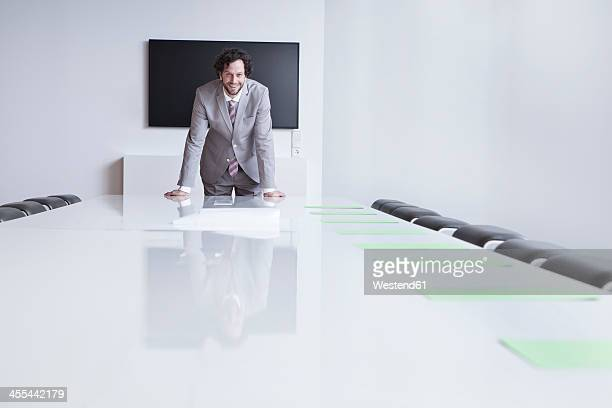 Germany, North Rhine Westphalia, Cologne, Portrait of businessman leaning on conference table, smiling