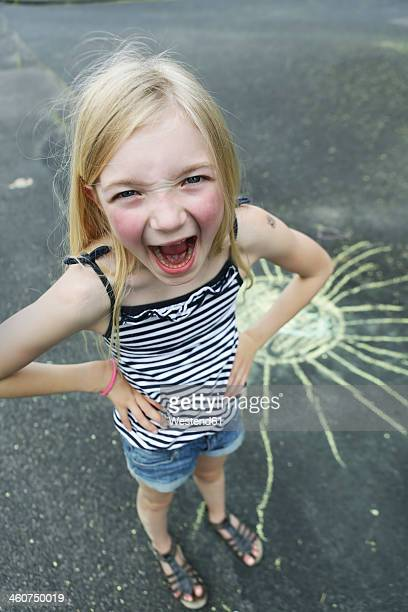 Germany, North Rhine Westphalia, Cologne, Portrait of girl drawing sun on street, smiling, close up