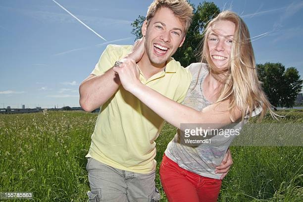Germany, North Rhine Westphalia, Duesseldorf, Couple playing in grass, smiling
