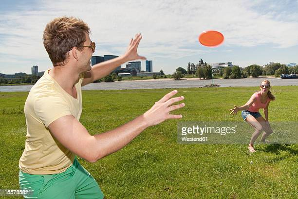 Germany, North Rhine Westphalia, Duesseldorf, Couple playing with frisbee