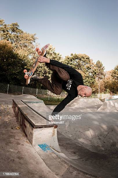 Germany, North Rhine Westphalia, Duesseldorf, Mature man jumping with skateboard