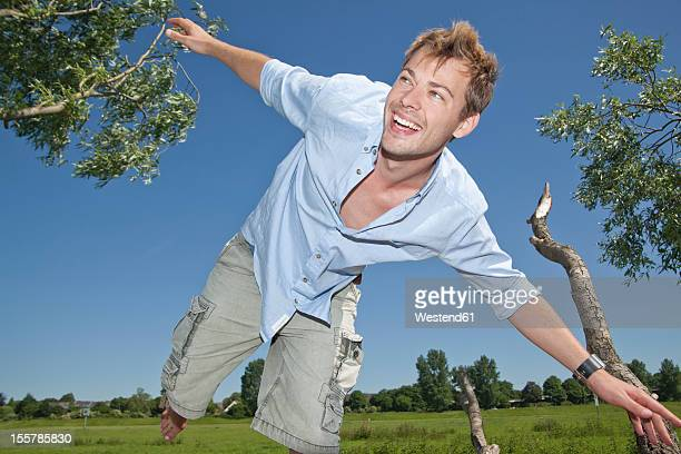 Germany, North Rhine Westphalia, Duesseldorf, Mid adult man playing with tree, smiling