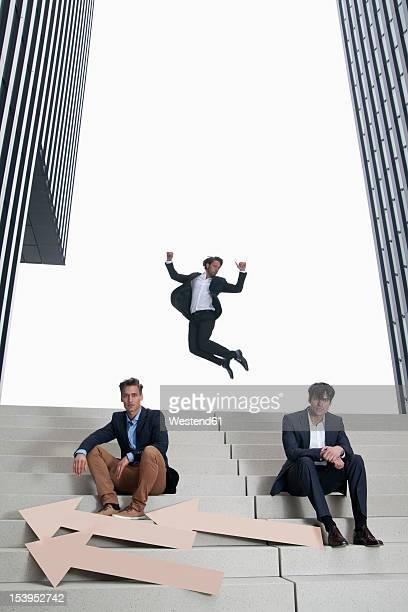 Germany, North Rhine Westphalia, Duesseldorf, Two businessman sitting on steps with arrows, while another man jumping in air