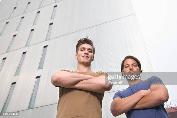 Germany, North Rhine Westphalia, Duesseldorf, Two trainees standing in front of building, smiling, portrait