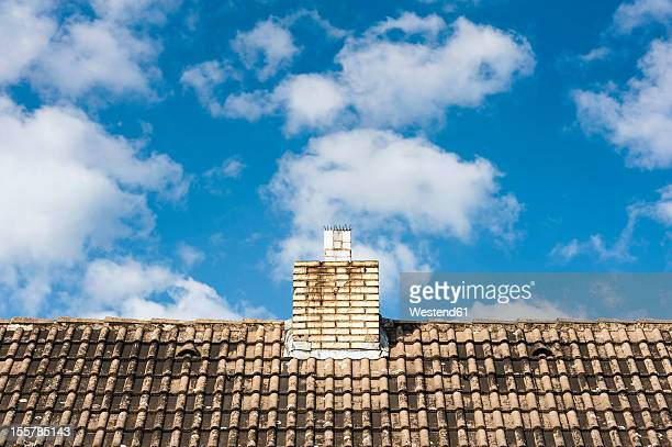 Germany, North Rhine Westphalia, Duesseldorf, View of tiled roof with chimney against clouds