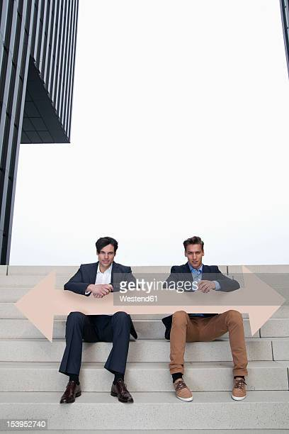Germany, North Rhine Westphalia, Duesseldorf, Young businessman sitting on steps with arrows in different directions