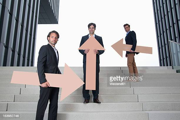 Germany, North Rhine Westphalia, Duesseldorf, Young businessmen standing on steps with arrows in different directions