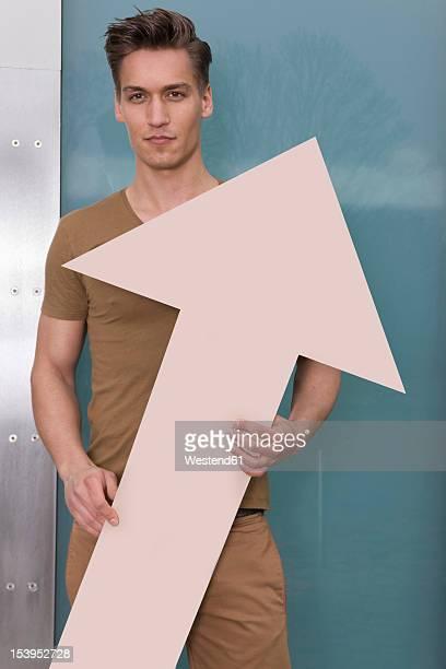Germany, North Rhine Westphalia, Duesseldorf, Young man standing with arrow, portrait