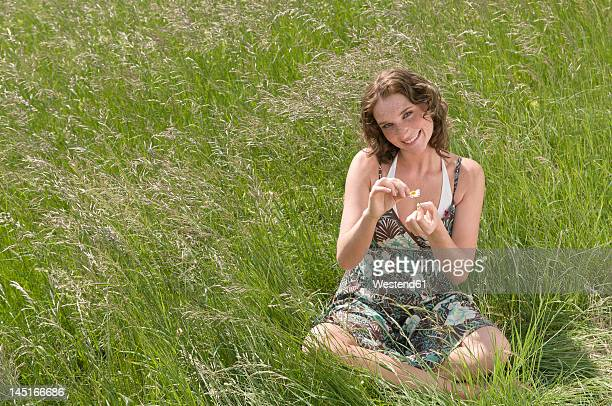 Germany, North Rhine Westphalia, Duesseldorf, Young woman plucking petals of flower, smiling, portrait