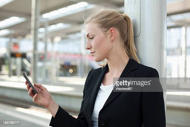 germany, north rhine westphalia, duesseldorf, young woman using smart phone at station - bahnhof stock-fotos und bilder